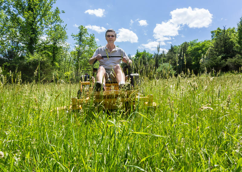 Senior man on zero turn lawnmower in meadow. Senior retired male cutting very deep grass in a meadow or field after leaving it to grow for far too long before royalty free stock photo