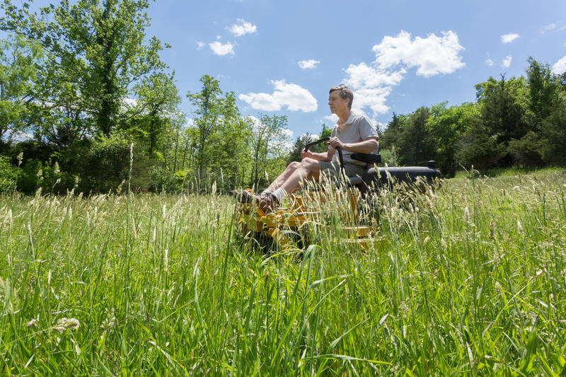 Senior man on zero turn lawnmower in meadow. Senior retired male cutting very deep grass in a meadow or field after leaving it to grow for far too long before stock photo
