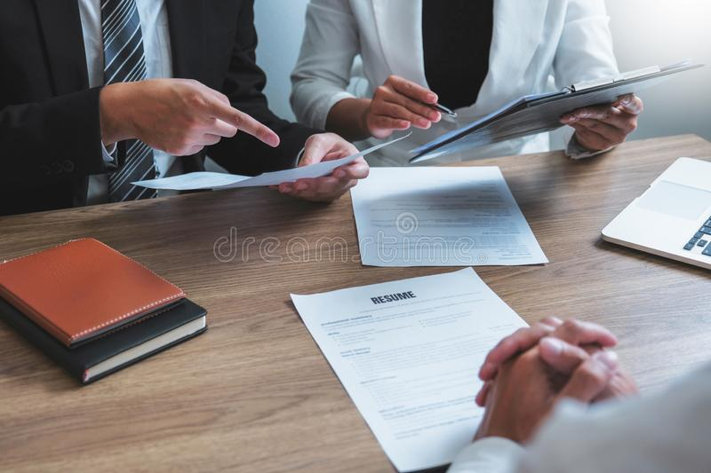 Senior manager HR reading a resume during a job interview employee young man meeting Applicant and recruitment. Senior manager HR reading a resume during a job royalty free stock images