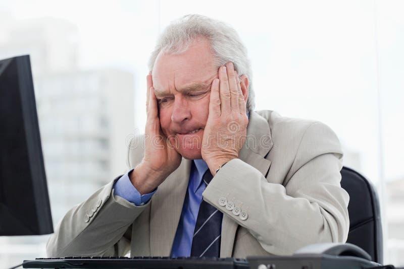 Senior manager turbato che lavora con un monitor immagine stock
