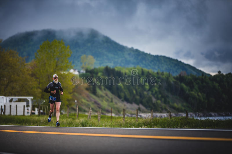 Senior Marathoner Alone on the side of the Road and Ocean. CARLETON, CANADA - June 4, 2017. During the 5th Marathon of Carleton in Quebec, Canada. Senior royalty free stock photography