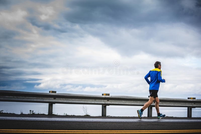 Senior Marathoner Alone on the side of the Road and Ocean. CARLETON, CANADA - June 4, 2017. During the 5th Marathon of Carleton in Quebec, Canada. Senior stock photos