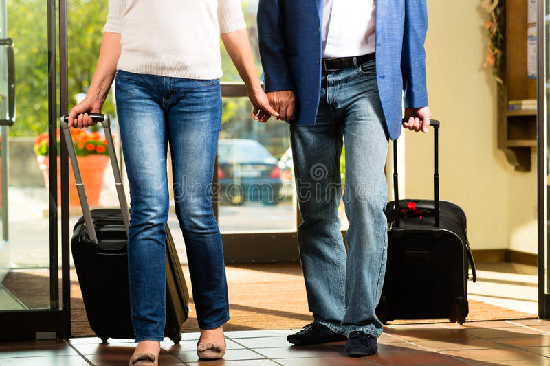 Senior married couple arriving at Hotel. Senior men and women - married couple - arriving at Hotel with their luggage royalty free stock photo