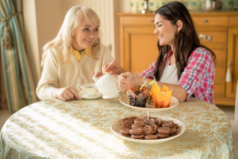 Senior matka pije herbaty z jej uśmiechniętą córką Desery stoją na stole zdjęcia royalty free