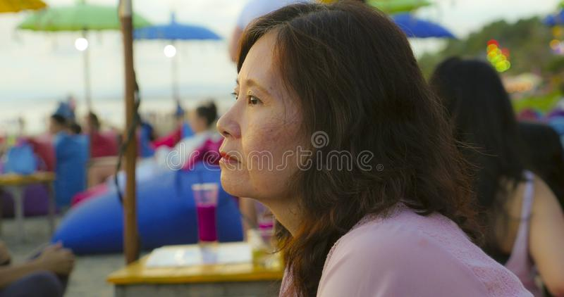 Senior mature Asian Chinese woman in her 50s or 60s looking relaxed and thoughtful sitting at tropical beach resort in Summer royalty free stock photos