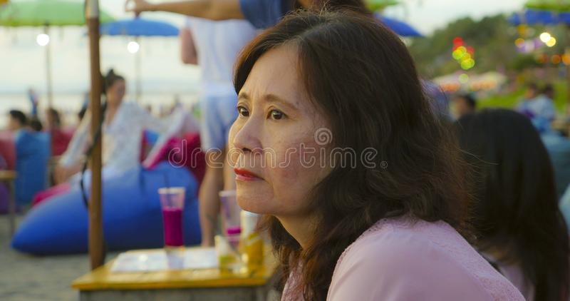 Senior mature Asian Chinese woman in her 50s or 60s looking relaxed and thoughtful sitting at tropical beach resort in Summer royalty free stock photo