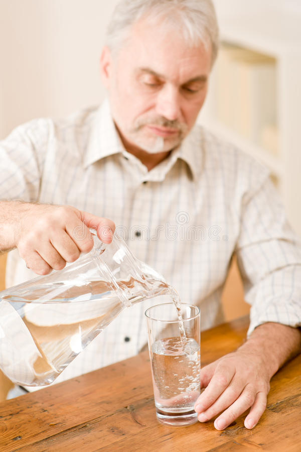 Senior mature man pour water sitting at table royalty free stock photo