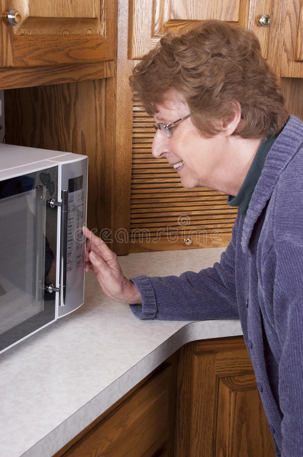 Senior Mature Woman Cooking Microwave Oven Kitchen. Smiling senior mature woman and grandma is cooking dinner with her modern microwave oven while in her kitchen royalty free stock images