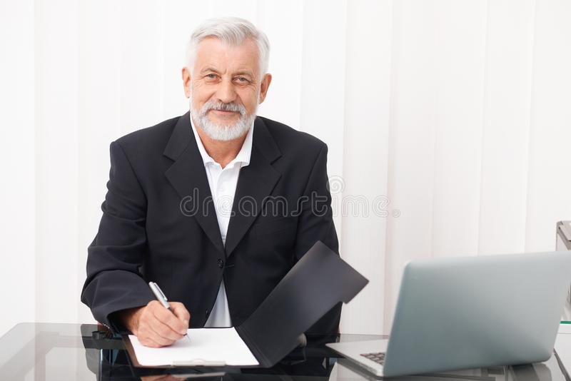 Senior medical practitioner smiling and looking into camera. royalty free stock image