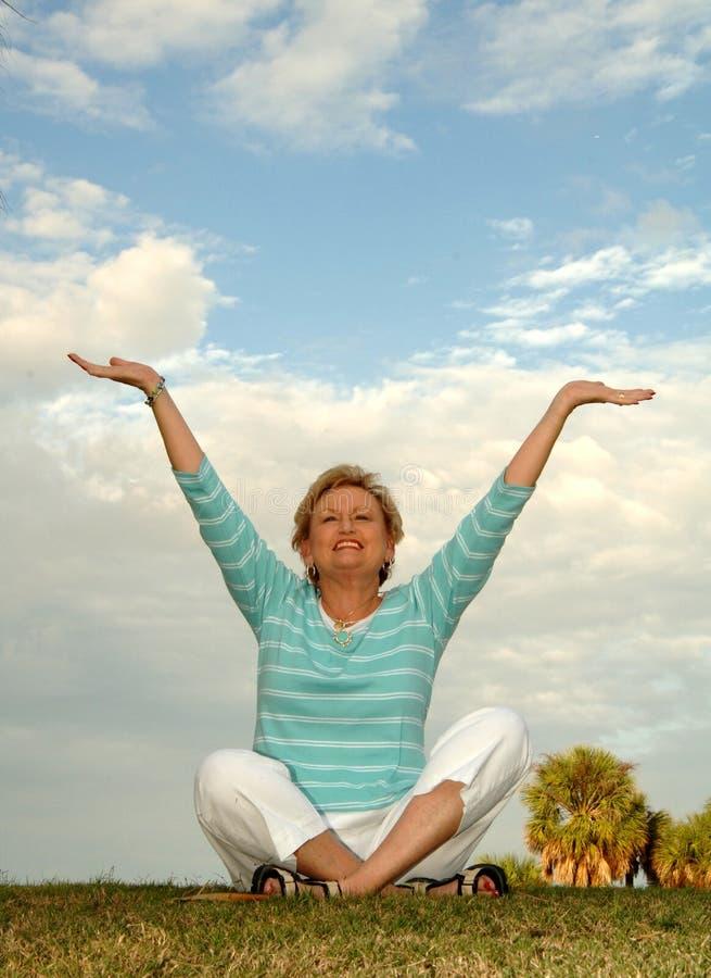 Senior meditation/praise. A senior woman sitting on a hill in a meditation/praise pose royalty free stock image