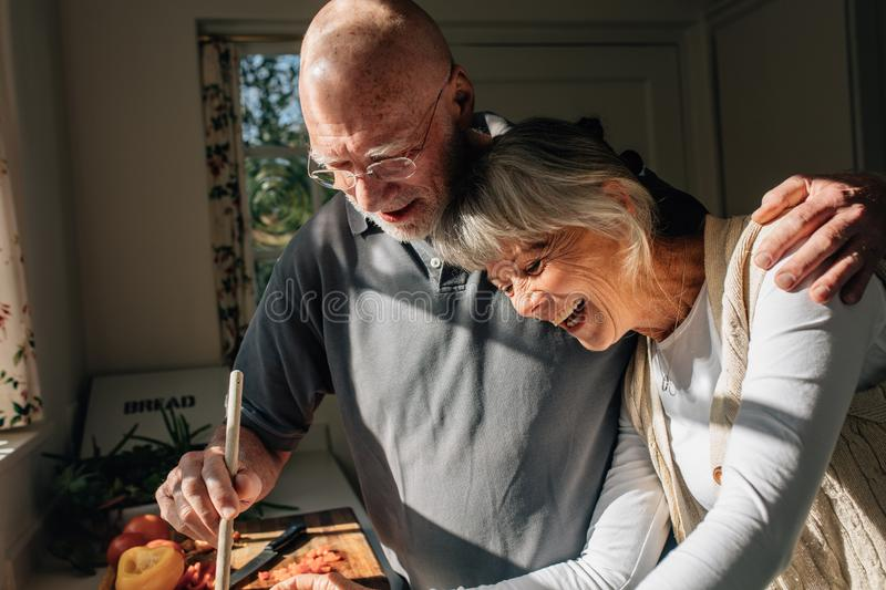 Senior man cooking food holding his wife in his arm standing in kitchen. Senior couple having good time cooking food together at stock photo
