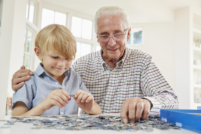 Senior man and grandson doing a jigsaw puzzle at home. Senior men and grandson doing a jigsaw puzzle at home royalty free stock photo