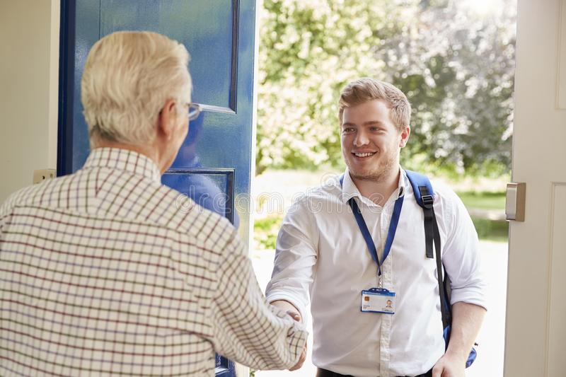 Senior man greeting male care worker making home visit. Senior men greeting male care worker making home visit royalty free stock photography