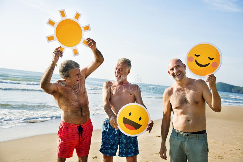 Senior men having fun on the beach. With emoji royalty free stock image