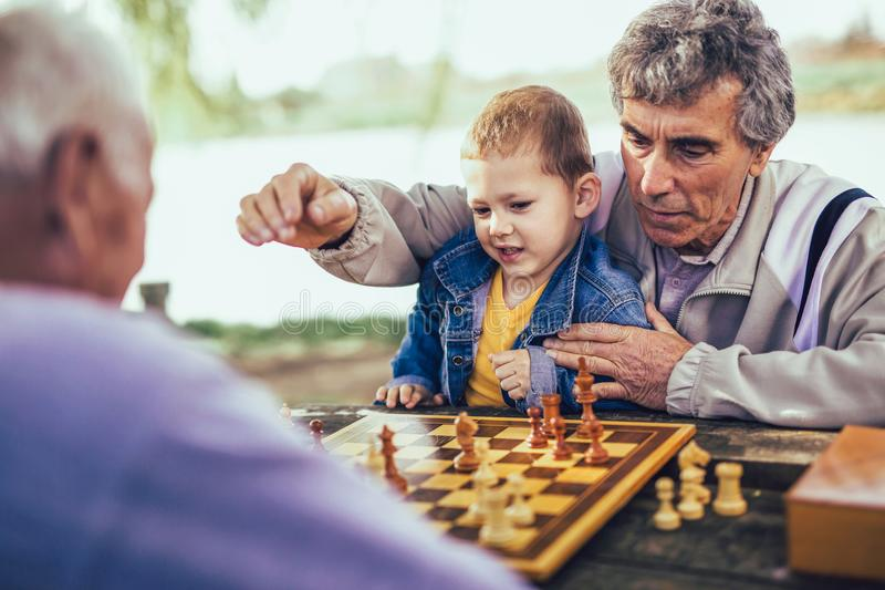 Senior men having fun and playing chess at park. Active retired people, old friends and free time, two senior men having fun and playing chess at park, spend royalty free stock images