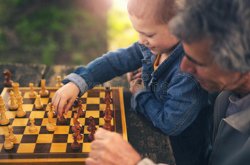 Senior men having fun and playing chess at park, spend time with grandson. Active retired people, old friends and free time, two senior men having fun and royalty free stock photography