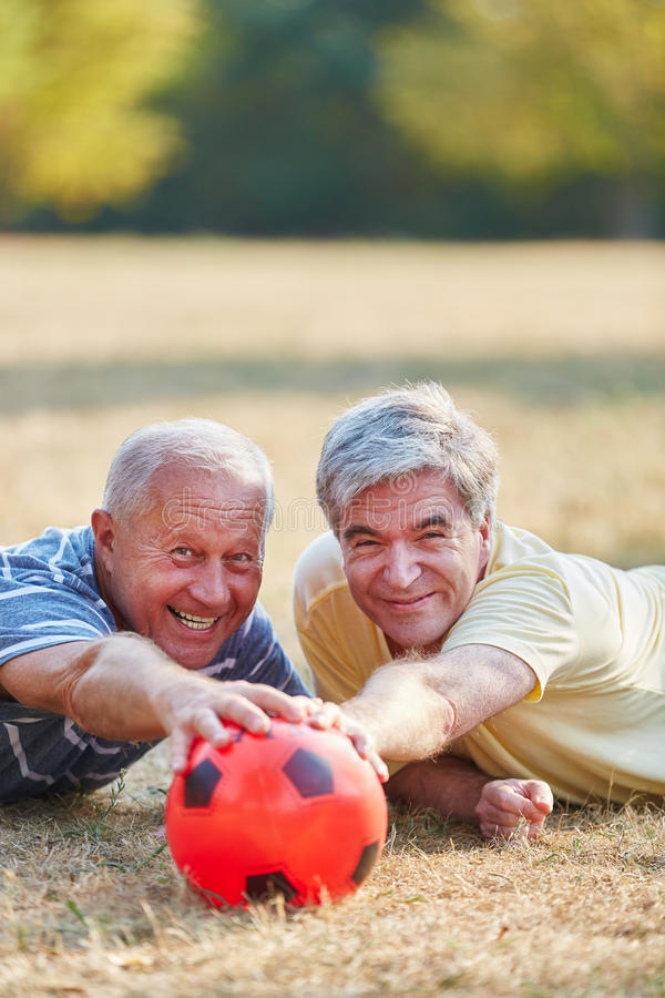 Senior men having fun while playing soccer. In the nature royalty free stock images