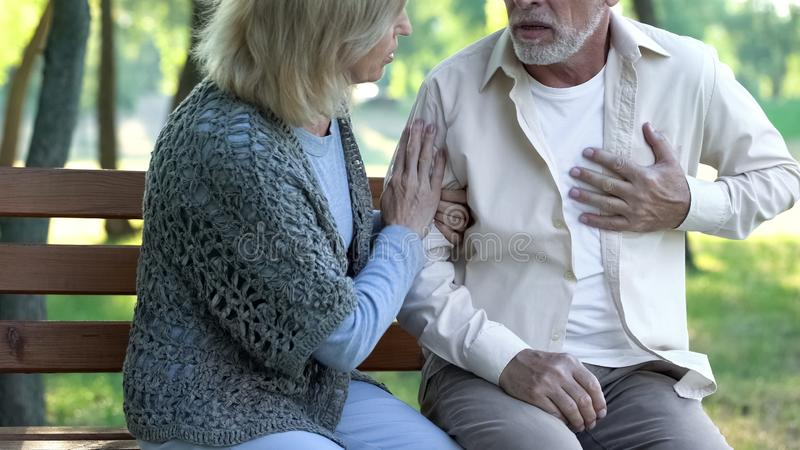 Senior man having heart attack during walk with wife, cardio problems healthcare. Senior men having heart attack during walk with wife, cardio problems stock photo