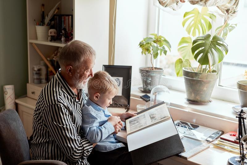 Grandfather and grandson on sofa at home. Grandpa and children watching old photos stock photo
