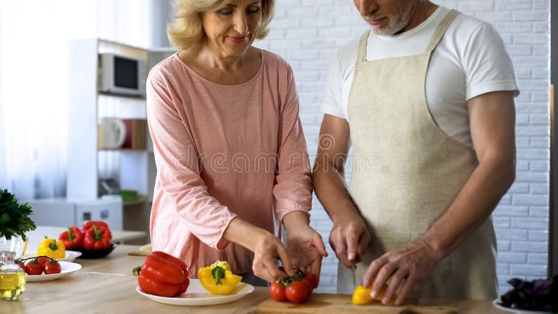 Senior man and loving wife cooking healthy vegetable lunch in kitchen, family stock images