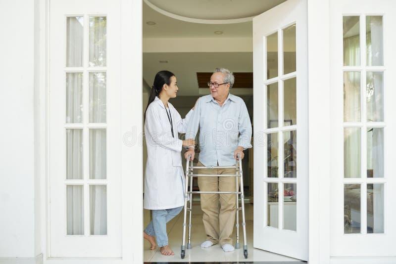 Senior man with nurse is going to walk royalty free stock image