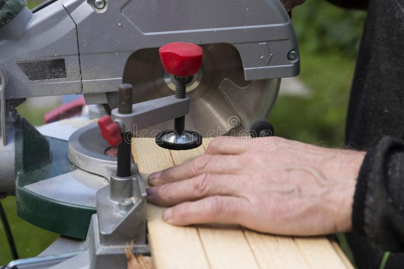 Senior men preparing wood materials with rotary saw stock image