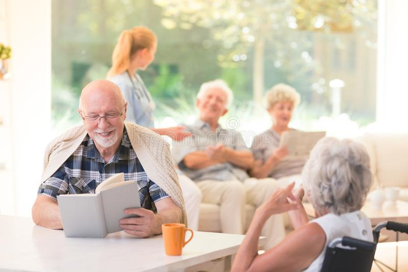 Smiling senior man reading book. Senior men reading a book and smiling while sitting with a friend at a table in nursing house stock image