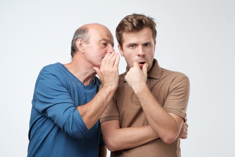 Senior man sharing secret or whispering gossips into his son ear. Telling family secret concept royalty free stock images