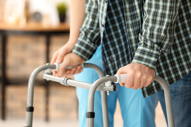 Senior man with walking frame and young caregiver,. Senior men with walking frame and young caregiver, indoors royalty free stock photography