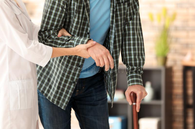 Senior man with walking stick and young caregiver,. Senior men with walking stick and young caregiver, indoors stock photography