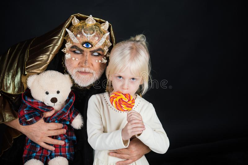 Senior man with white beard dressed like monster telling story to little girl. Fairytale concept. Man with thorns or. Senior men with white beard dressed like royalty free stock photography