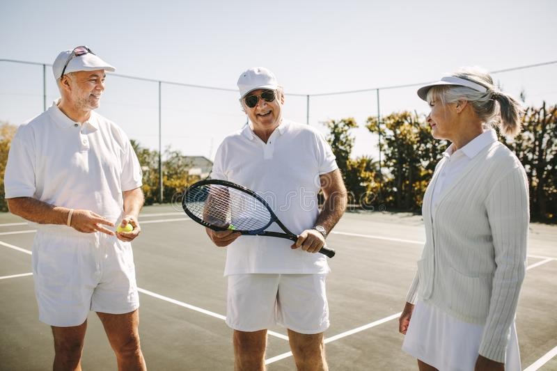 Senior men and a woman playing tennis stock image