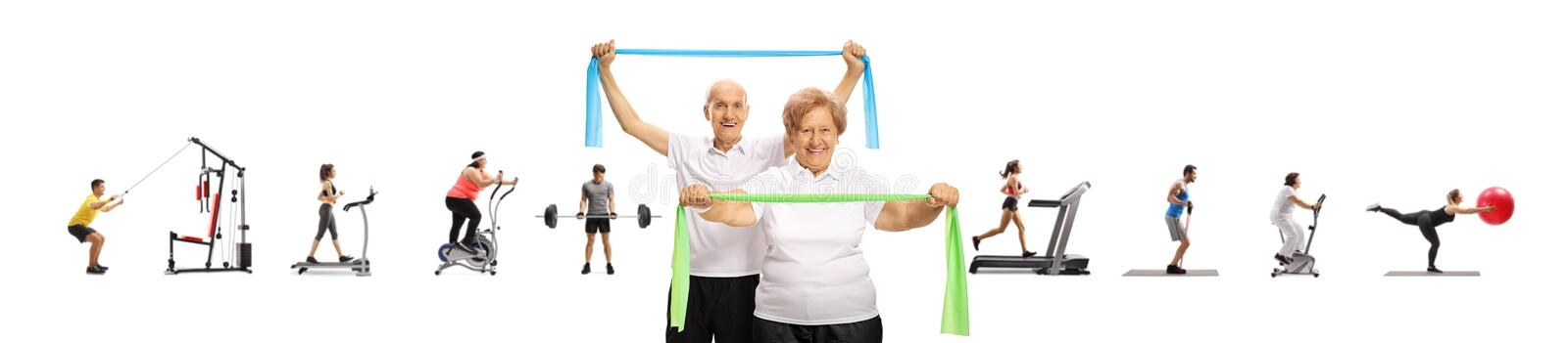 Senior man and woman with ellastic bands and many people exercising behind. Senior men and women with ellastic bands and many people exercising behind isolated stock image