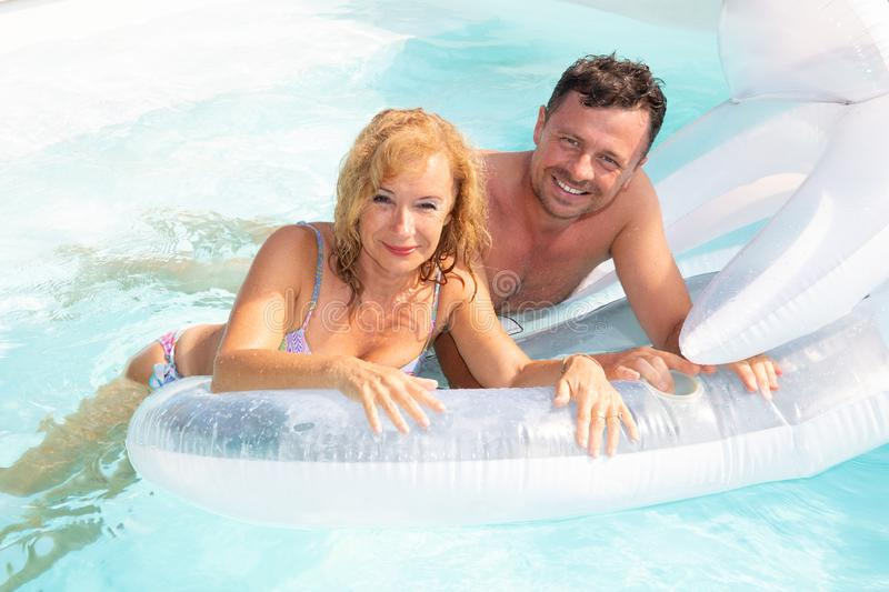 Senior man and woman with large buoy in pool in summer time vacation royalty free stock photography