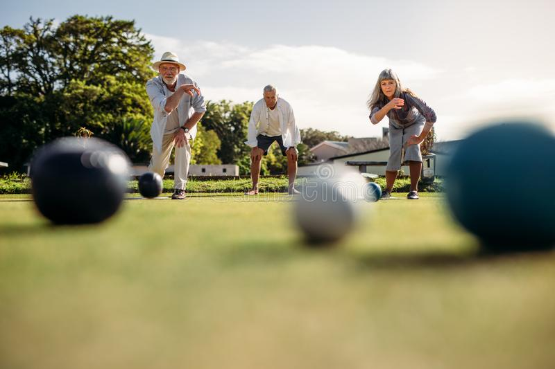Senior people playing boules in a park stock images