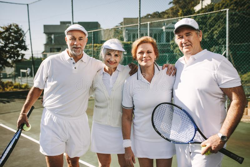 Senior men and women standing together on a tennis court stock image