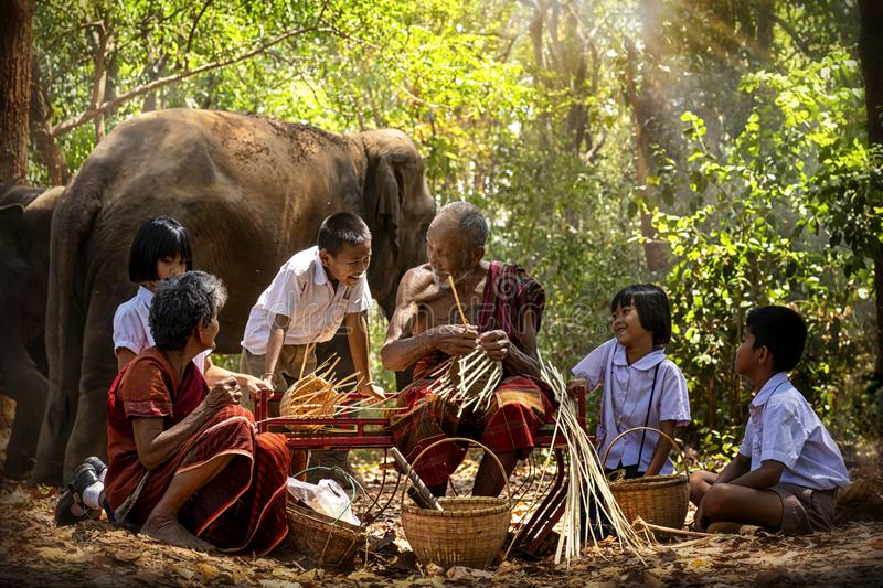 Senior Men and women are weaves basket with nephew and granddaughter and a big elephant in the forest. Old man and woman weaves stock photos