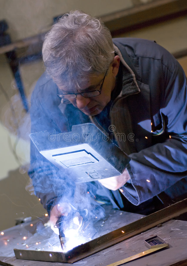 Senior metalworker welding stock photos