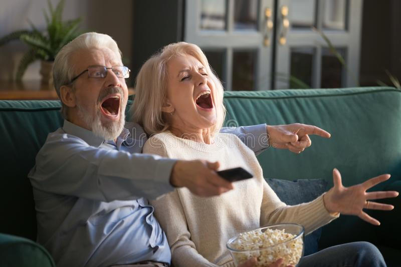 Elderly husband and wife cheering favorite sport team. royalty free stock photos