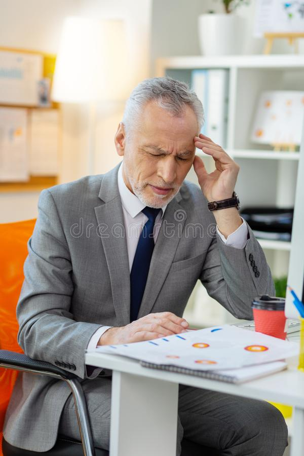 Senior miserable man having extreme headache at work stock photography