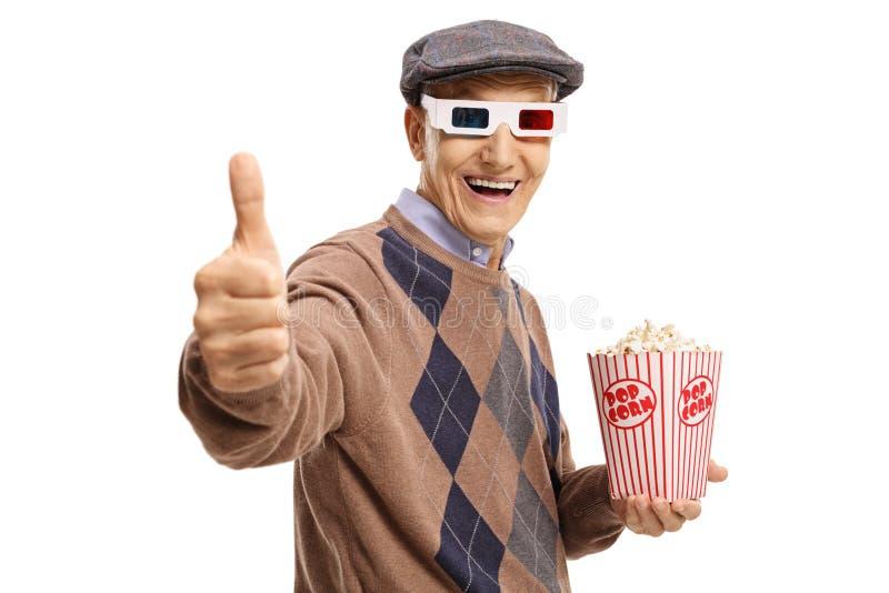 Senior mit den Gläsern 3D und Popcorn, die Daumen herauf Zeichen herstellen stockfotografie