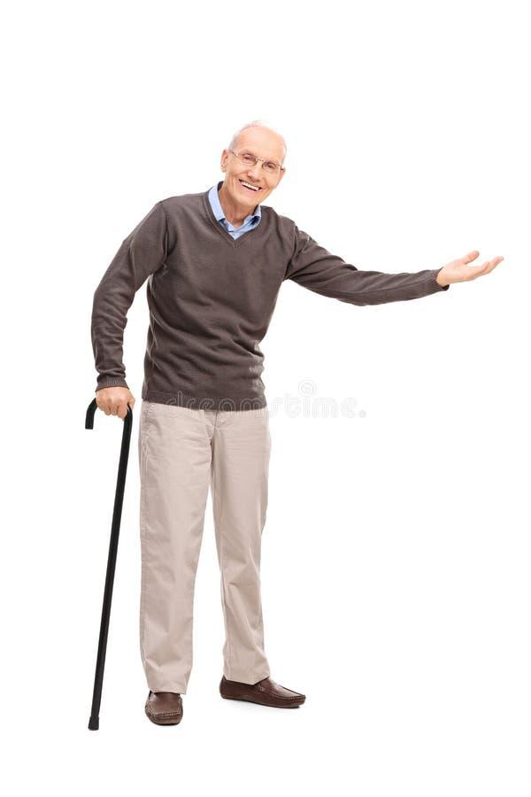 Senior mit einem Stock gestikulierend mit seiner Hand stockfotos