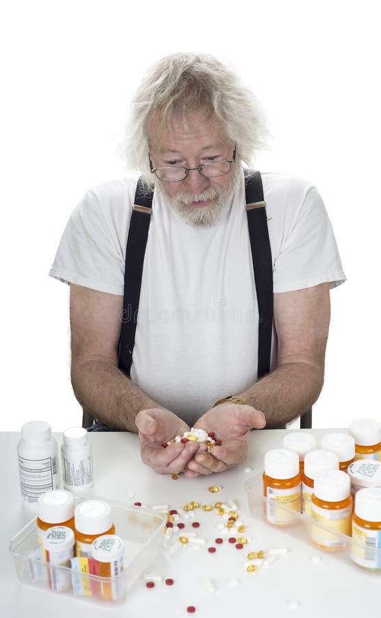 Senior Mit Vielen Verordnungen Und Einer Handvoll Pillen Lizenzfreie Stockfotos