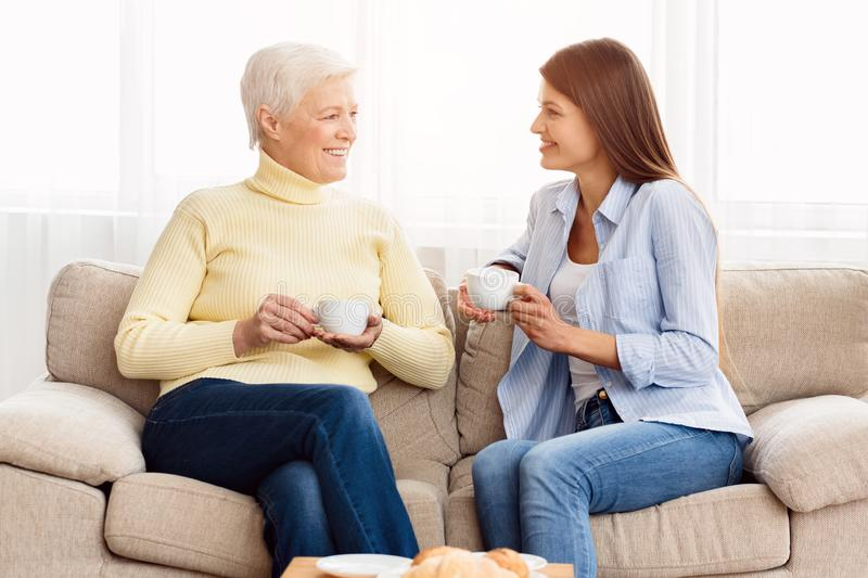 Senior mom and adult daughter talking and drinking coffee stock image