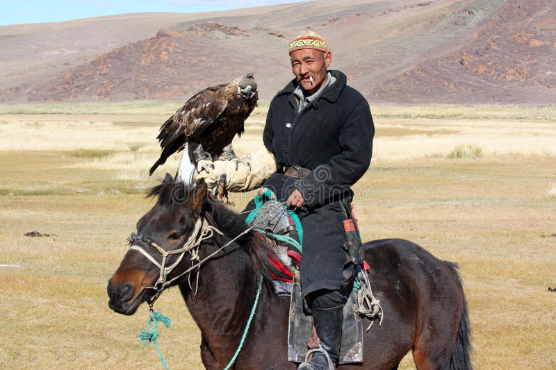 The senior Mongolian horseman with eagle. The senior Mongolian horseman in traditional clothing with golden eagle stock images
