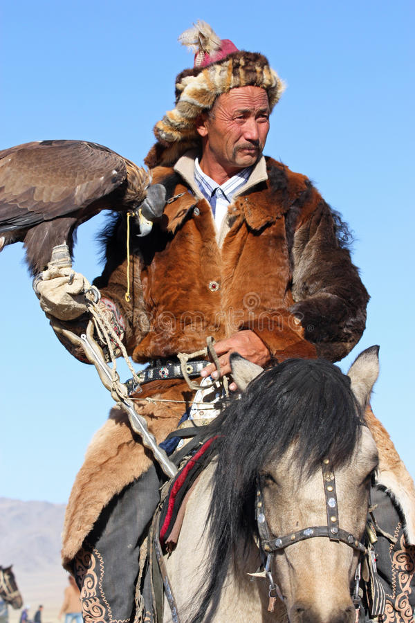 Senior Mongolian horseman in traditional clothing. With golden eagle stock photos