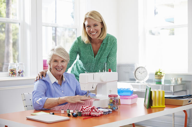 Senior Mother And Adult Daughter Use Sewing Machine At Home stock photo