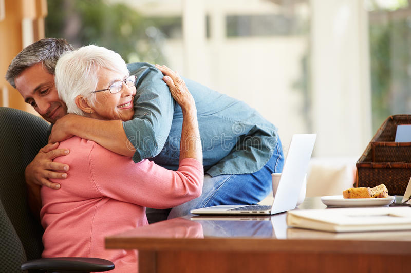 Senior Mother Being Comforted By Adult Son. At Home Hugging Each Other stock photography
