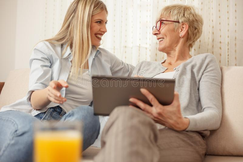 Mother and daughter laughing and looking at each other while using a tablet royalty free stock image