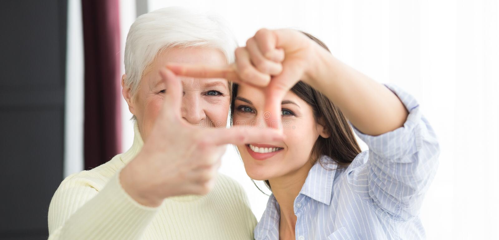 Senior mother and daughter making frame with fingers stock photo
